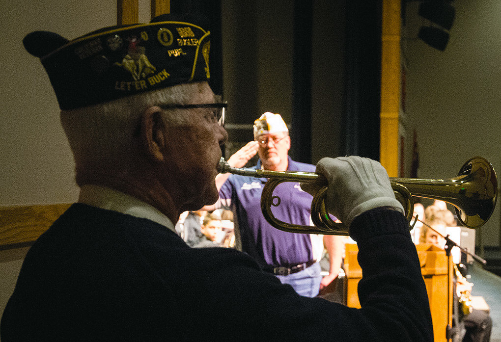 Veteran Tom Bibbey plays taps while Jerry Clark salutes in the background during a celebration of Veterans Day at Powell High School Monday. Clark is commander of Hughes-Pittinger Post 26 in Powell and the 2nd Vice Commander of the American Legion for the state of Wyoming.