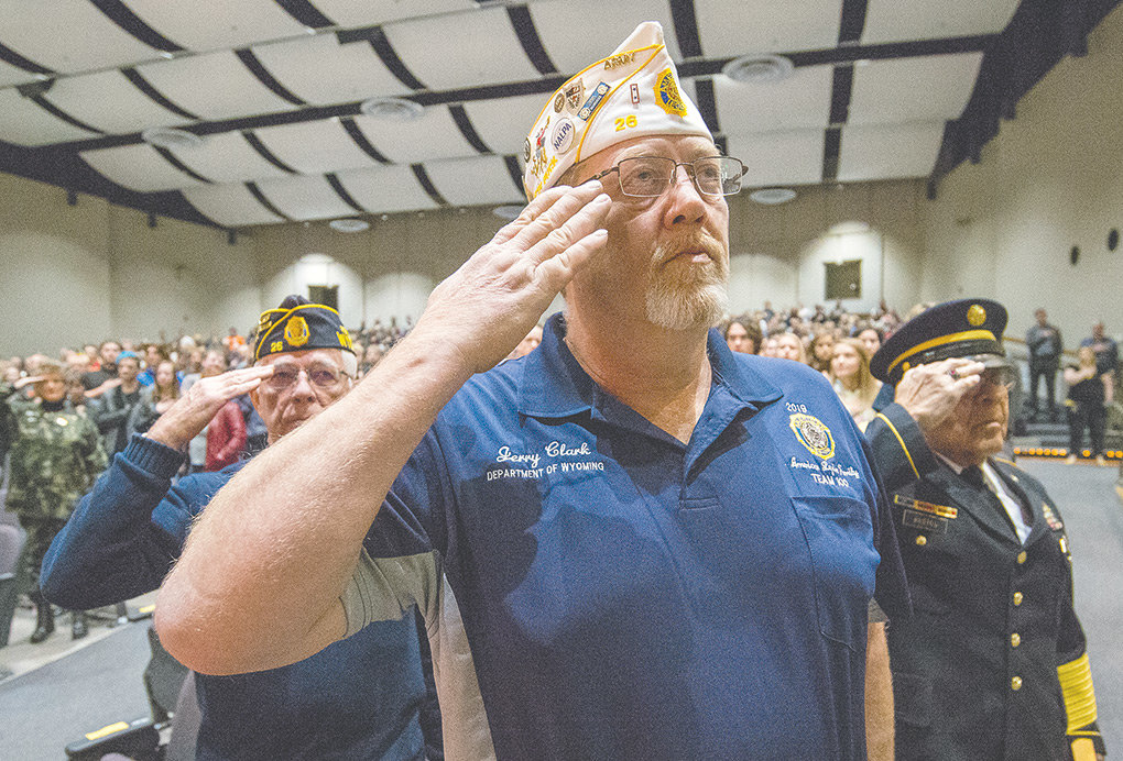 Veterans Jerry Clark (front), Tom Bibbey (back left) and John Bustos (back right) salute the flag during the playing of the National Anthem during a celebration of Veterans Day at Powell High School Monday. The local American Legion post is embarking on a new project to honor all of the Powell area's veterans from the past 100 years.