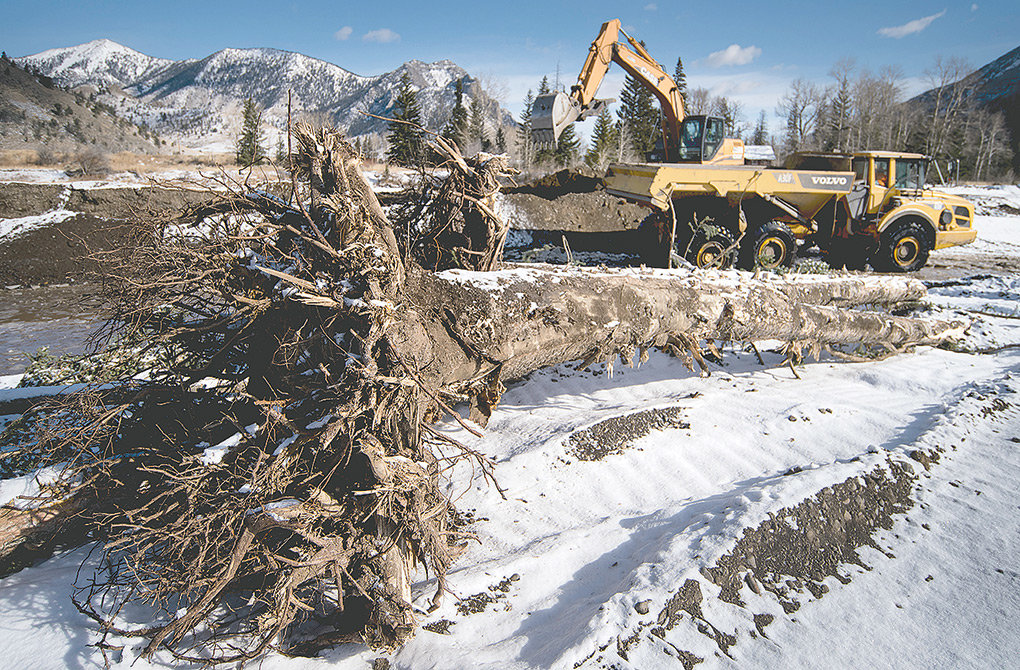 Construction crews with Shamrock Environmental Corporation work to place toe wood — tree trunks complete with root structure — to help absorb energy as Sunlight Creek flows during high water.