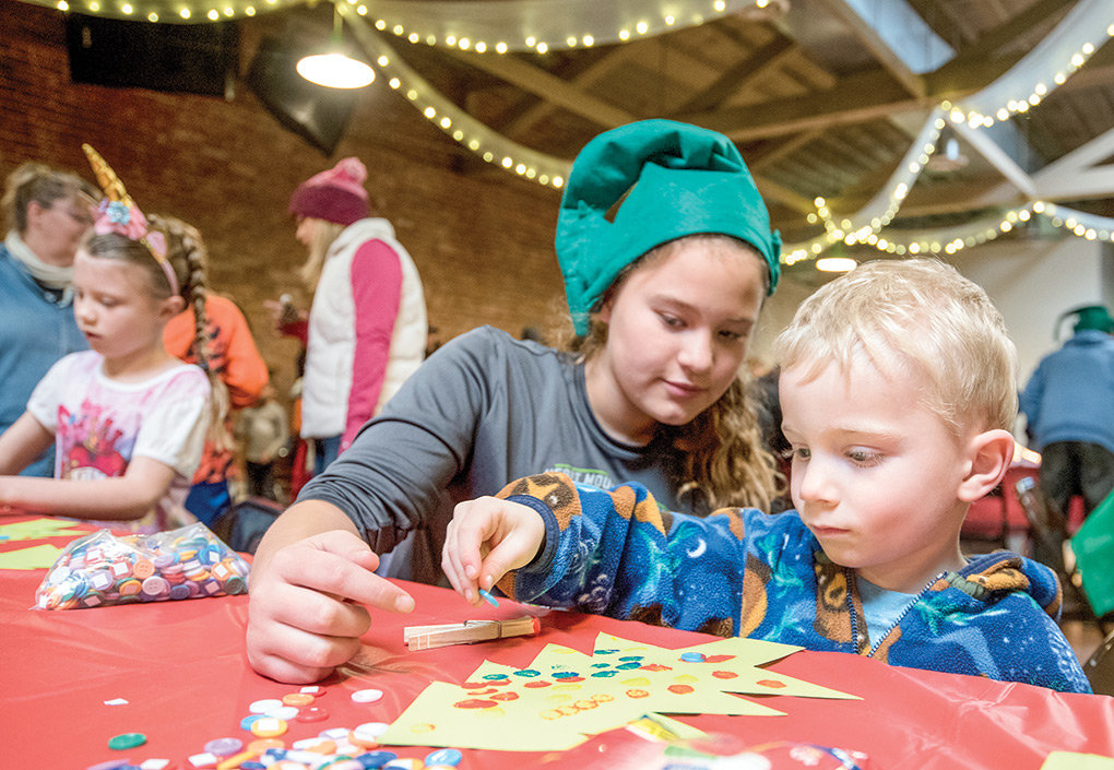 Carter Sheets works on a craft project at The Commons with Santa's workshop volunteer Hadley Cooper on Friday morning.