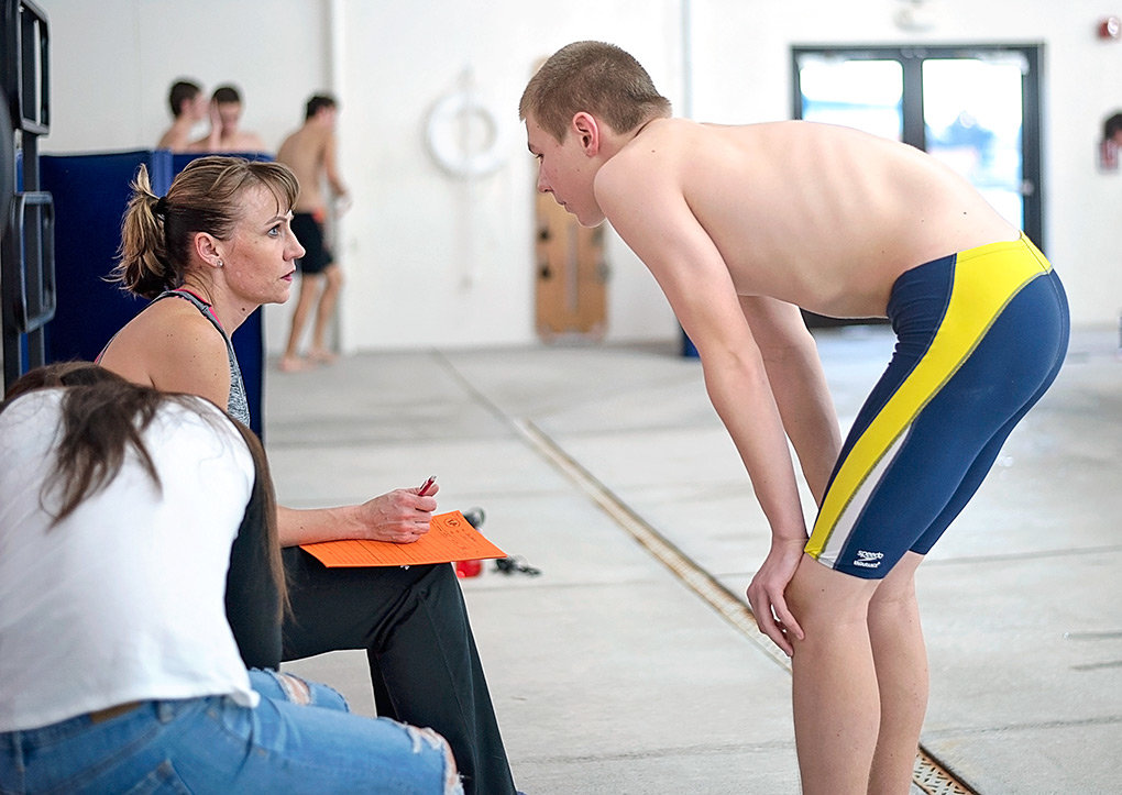PHS head boys' swimming and diving coach Stephanie Warren talks with freshman swimmer Ben Hawley during practice at the Powell Aquatic Center on Tuesday.