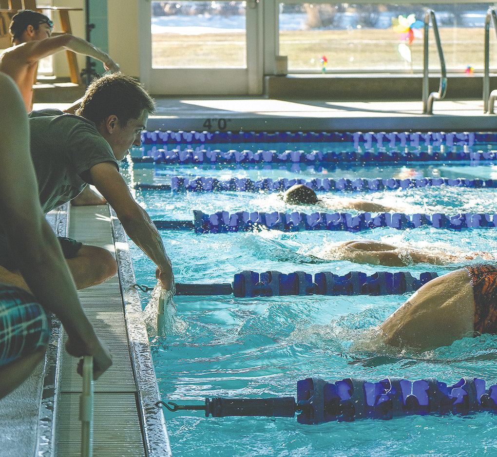 Powell swimmer Jay Cox runs the lap-counting board for Ben Cannizzaro as he swims the 500 freestyle at the quad meet held in Cody Saturday. As a team, Powell finished 139 points ahead of host team Cody. The Panthers' next action in the pool is slated for Saturday in Riverton.