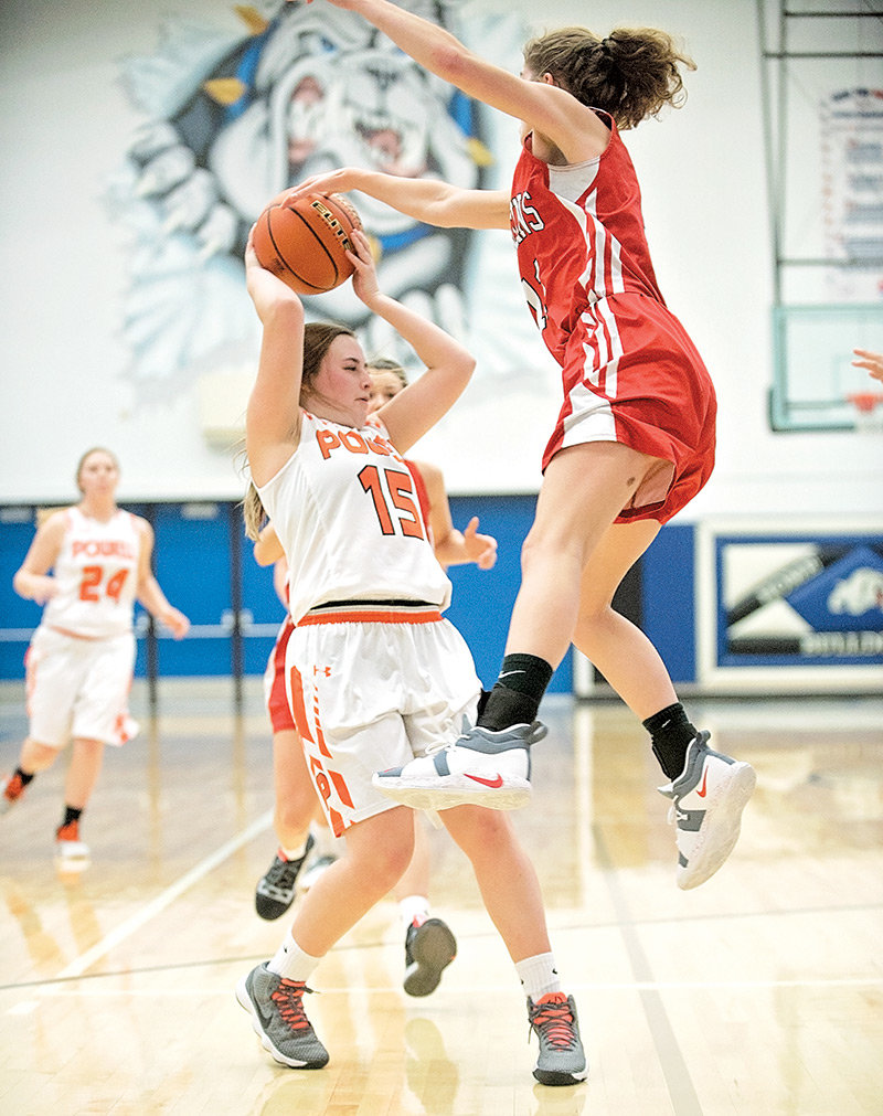 Lady Panther Katie McKenzie dodges Rawlins' Miranda Wagner Friday during the opening round of the East-West Classic in Lovell. Powell won the game 39-34 for its first win of the season.
