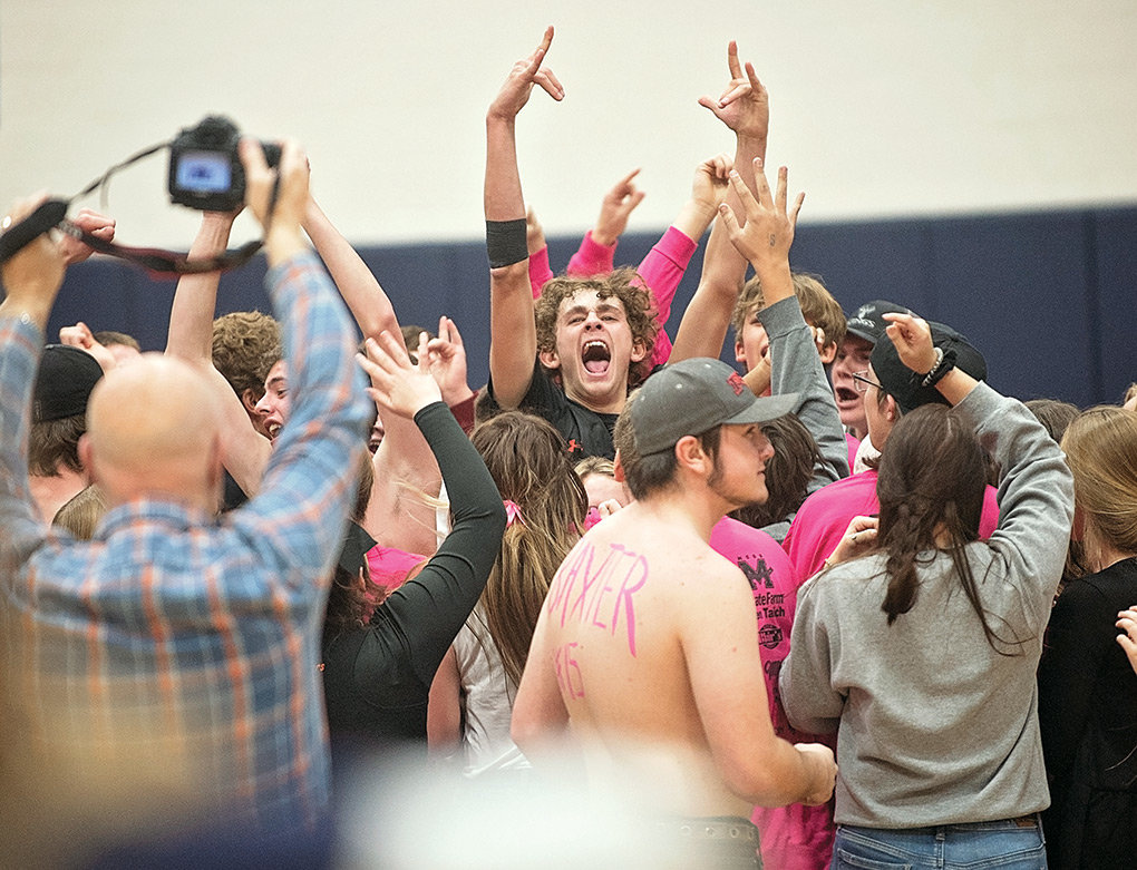 Powell's Jesse Brown celebrates as fans storm the court following the Panthers' Friday upset of the 4A Cody Broncs at Cody High School. The cross county rivalry game featured 10 lead changes, with Powell holding on late for the 73-69 win.