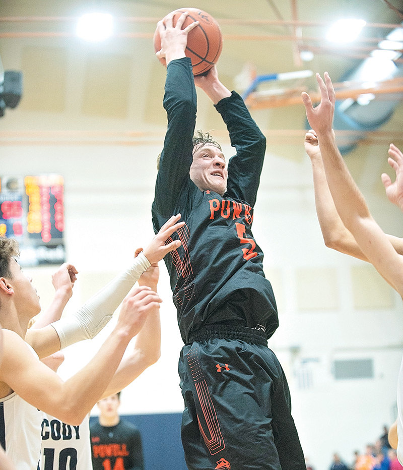 Powell High School senior William Preator pulls down a rebound over a crowd of Cody Broncs on Friday at Cody High School. Preator led the Panthers with 21 points, helping Powell pick up its first win of the season, 73-69 over Cody.