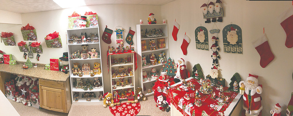 The living area downstairs features displays of Santas, Christmas stockings, gift bags, and an assortment of holiday figurines and Western-themed decorations.