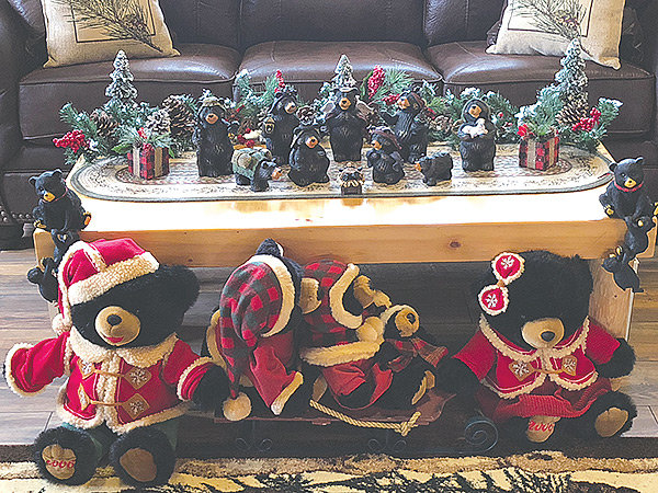Stuffed black bears dressed for Christmas sit in front of a coffee table topped by a Christmas nativity scene featuring black bears.