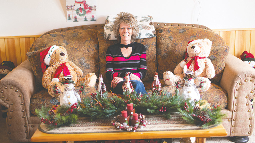 Shana Bartle of rural Powell loves to decorate her home for Christmas. Above, she sits on a couch in her living room, surrounded by Christmas teddy bears and other holiday decor.