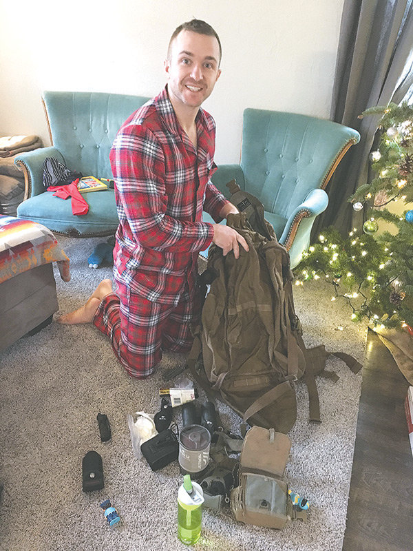 Garrett Burbank opens his pack while in his jammies on Christmas morning. The pack was anonymously returned in a trash bag following its theft from Burbank's truck several days earlier.