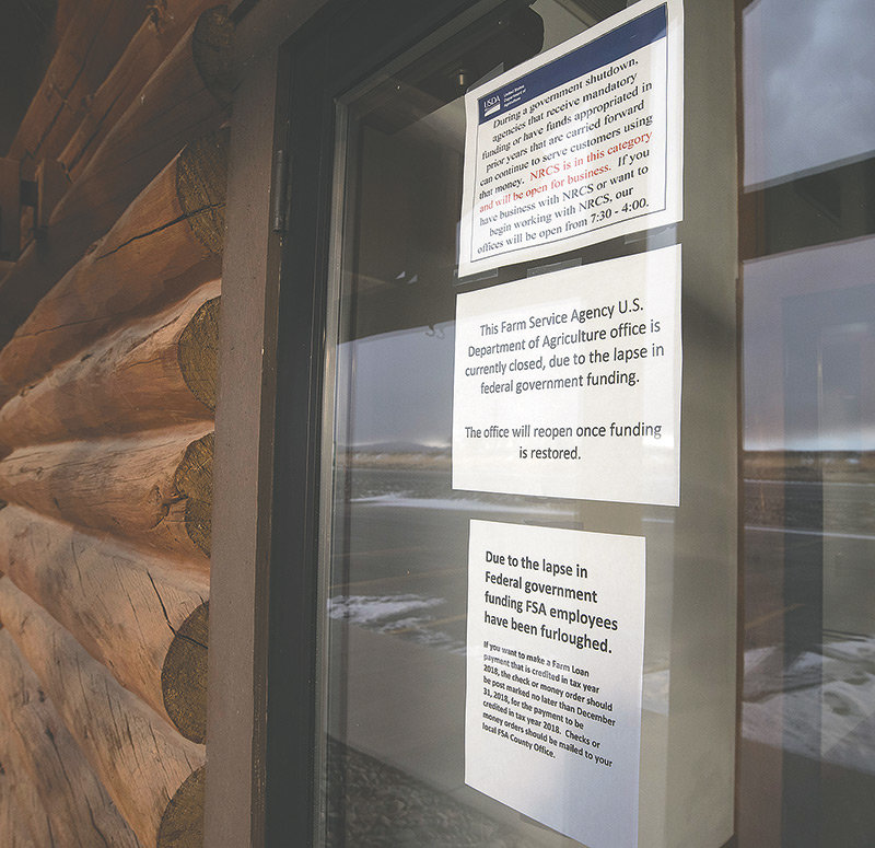 Signs posted at the Farm Service Agency outside Powell notify visitors that the employees have been furloughed and the office closed during the partial government shutdown, while the Natural Resources Conservation Service remains open.