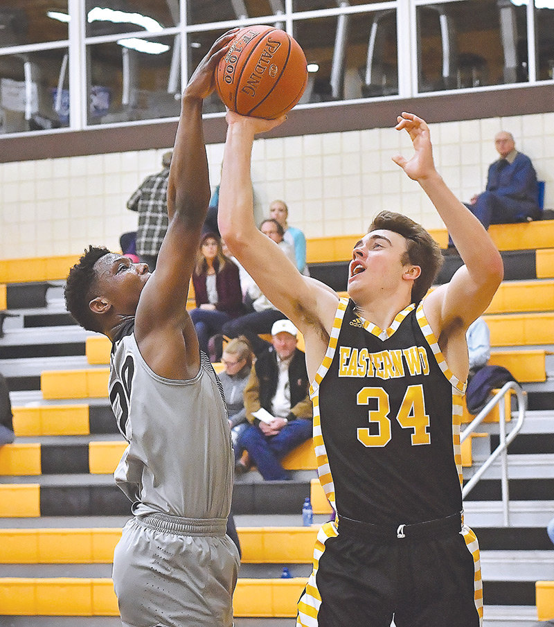 NWC sophomore Calvin Fugett blocks a shot from Eastern Wyoming's Jacob Pfaffinger Saturday at Eastern Wyoming College. The Lancers won the game in double overtime 81-78.