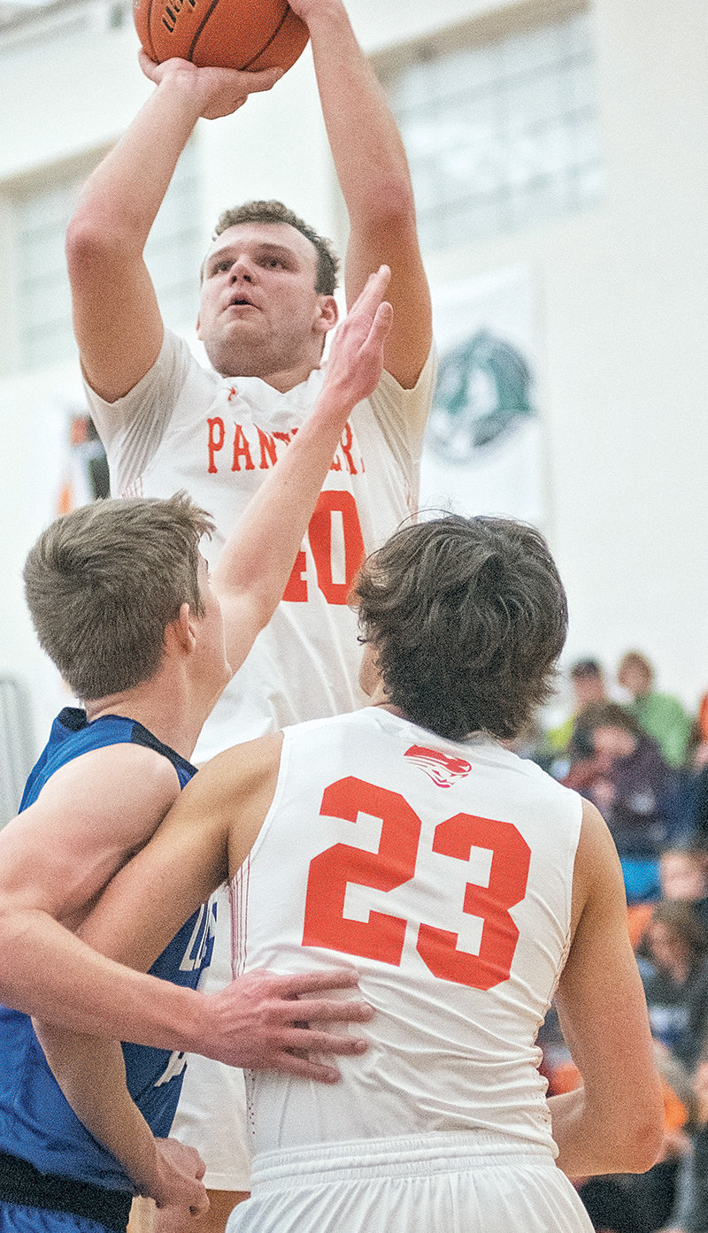 Panther senior Carson Heinen pulls up for a shot over teammate Dalton Woodward and a Lovell defender on Friday at Panther Gym. Powell won the 3A Northwest rivalry game, 38-29.