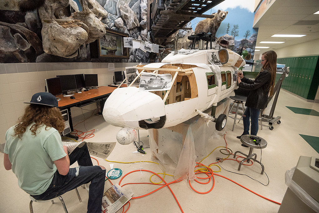 Colton Johannsen (left) and Hannah Saville work on a Blackhawk helicopter on Tuesday. It's the latest large-scale project that PHS students are creating.