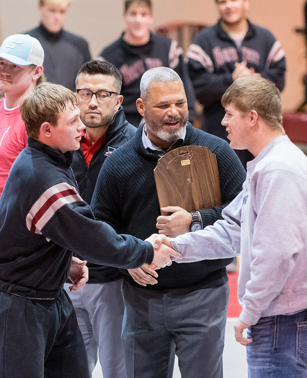 Northwest College head wrestling coach Jim Zeigler and 2018 Apodaca award winner Jeffrey Oakes congratulate 2019 award winner Porter Fox (left) at a Friday night ceremony.