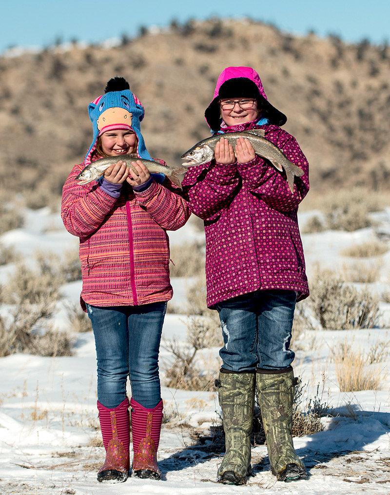 Tempe Day, 8, and Isi Tobin, 9, show off their prize-winning trout after the weigh-in during the Meeteetse Ice Fishing Derby Sunday. The Powell students fished the two-day tournament and each weighed in two fish.