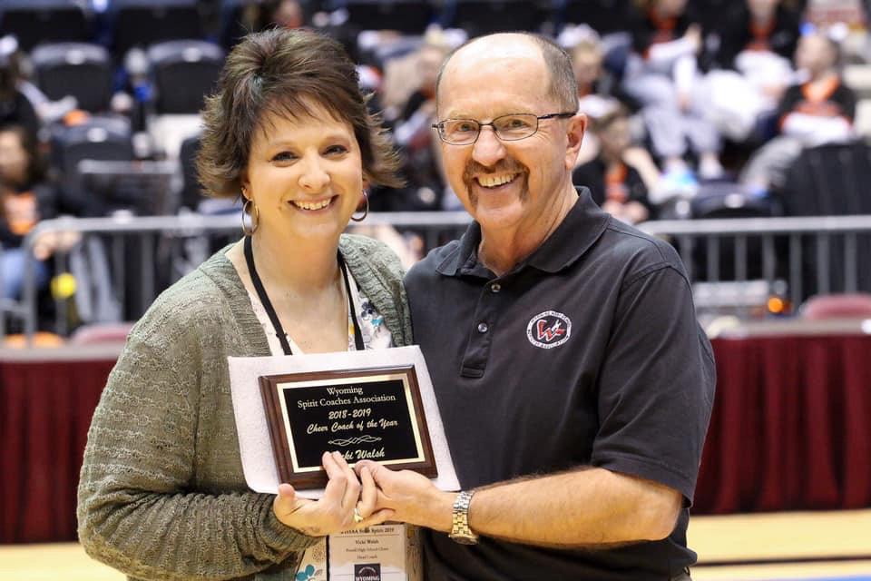 2018-19 Cheer Coach of the Year Vicki Walsh receives a plaque from WHSAA Commissioner Ron Laird.