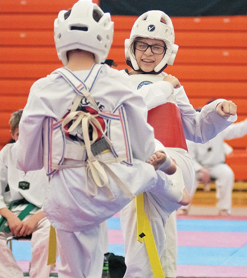 Lone Wolf Martial Arts' Jasmin Simonson, right, squares off against her brother Aiden in sparring at the Lone Wolf Taekwondo Championships at Panther Gym earlier this month. A dozen teams from around the region participated in the event.