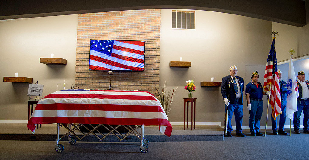 Joseph J. Mulvaney's casket is covered with the American flag in the chapel at Ballard Funeral Home on Friday while (from left) Jerry Clark, 2nd Vice Commander for the Department of Wyoming American Legion, Frank Cropanese, department chaplain, Jim Vandavart, District 4 commander and Jim Yockey, District 4 vice commander stand watch.