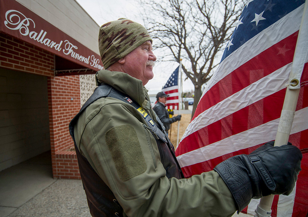 Sully Sullivan, of the Patriot Guard Riders, stands post with the American flag in hand outside Ballard Funeral Home in Cody Friday.