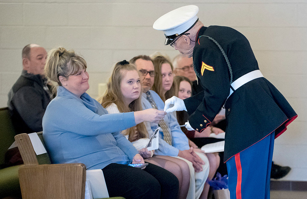 Shelley Statler, granddaughter of Joseph J. Mulvaney, is presented with a memorial pin by  Honor Guard member Bill Buntyn while the Statler family, including (from left) Kaylee, 17, Ron, Jenna, 13, Brittany, 15, and Deacon Rick Moser, watch from the front row.