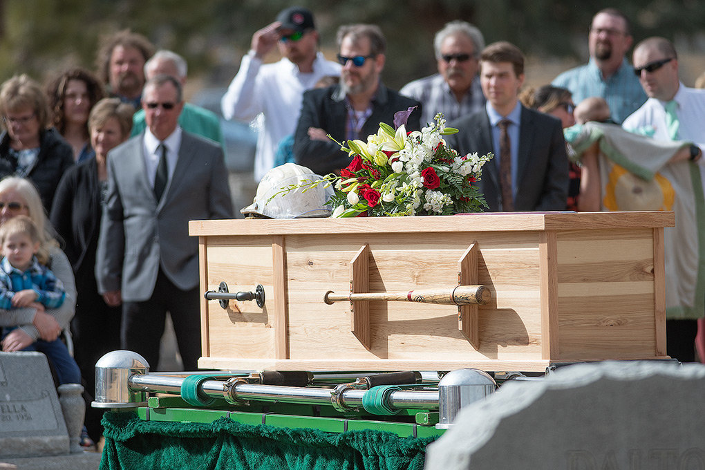 Adorned with flowers and his fire chief's helmet, Calvin Sanders' hand-made casket, with Louisville Sluggers and plumbing equipment as handles, awaits interment at Crown Hill Cemetery Wednesday east of Powell. Sanders, a firefighter, umpire and businessman, died last month following a 19-month battle with pancreatic cancer.