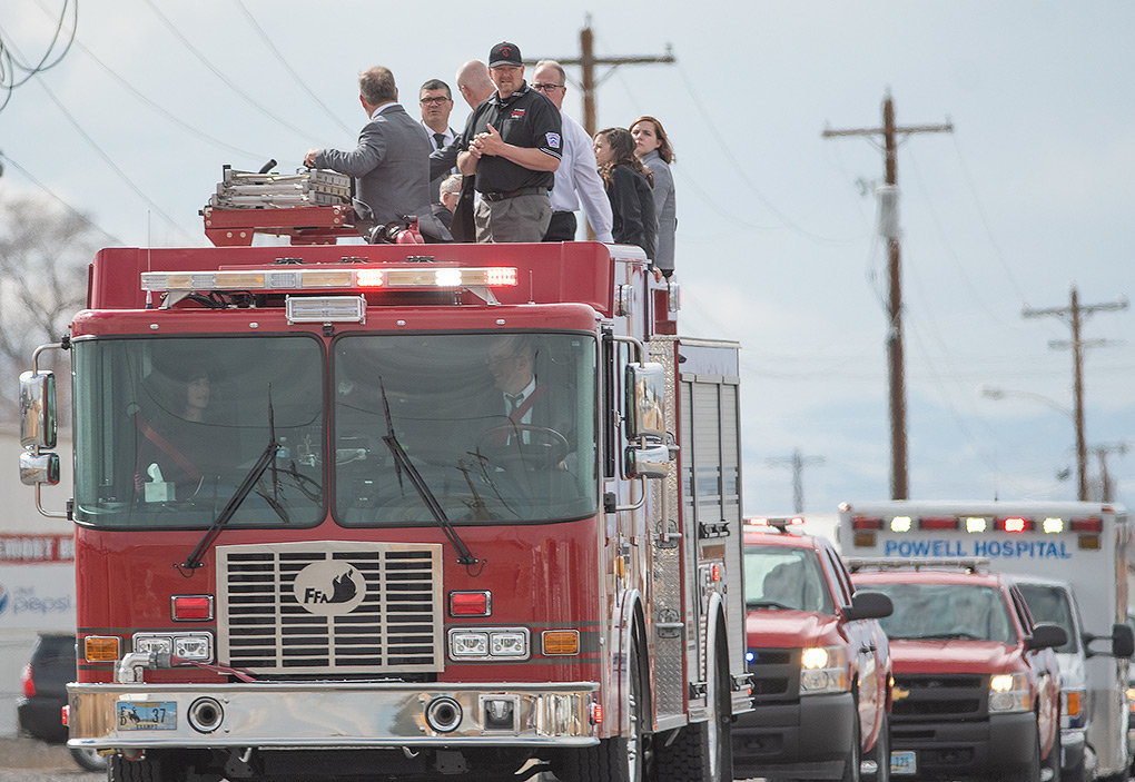 Family and friends of longtime firefighter Calvin Sanders ride atop a fire engine as part of a funeral procession to Crown Hill Cemetery Wednesday following Sanders' memorial service at Cabre Gym.