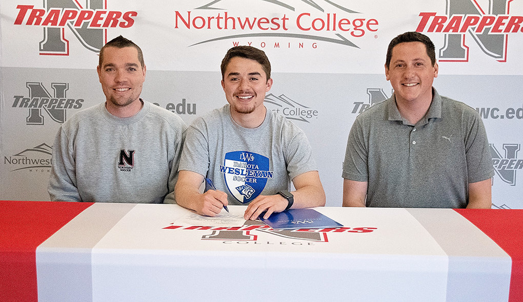 Former Trapper Edgar Meza (center) is joined by new men's soccer coach Ben McArthur (left) and NWC athletic director Brian Erickson as he signs his letter of intent to play for Dakota Wesleyan University in the fall.