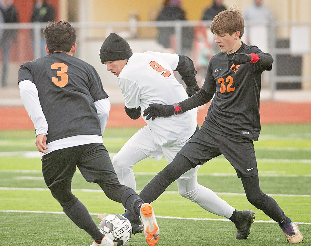 Panther midfielders Ernie Acevedo (left) and Garrett Morris (No. 32) surround Worland's Cole Venable during a Tuesday afternoon game at Panther Stadium. The battle of two of the top teams in 3A went to the Warriors, who took a 1-0 win.