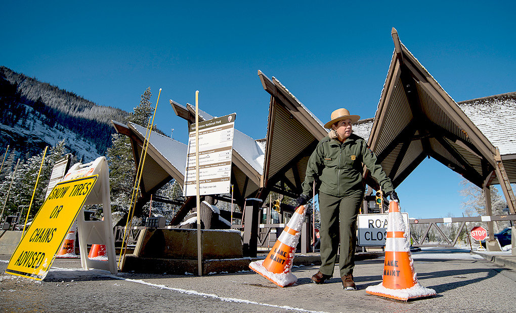 Park ranger Kimberly Kain clears the path to open the East Entrance gates on Friday.