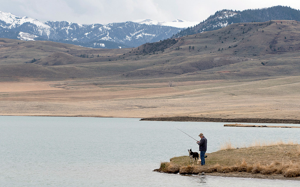 With his dog watching closely, a fisherman throws lures from the shore at Upper Sunshine Reservoir Sunday. The lakes are in the foothills of the Absaroka Mountain Range.