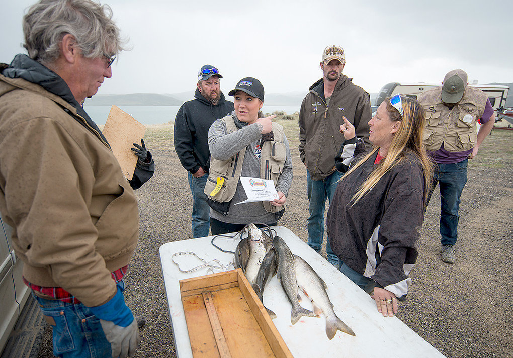 Mikayla Norman and Jodi Firnekas, of Powell, plead their case with Edward Porter, president of the Meeteetse Visitor Center, while questioning a rule in the tournament. The team, along with Rob Martin (back right) wanted to have six fish weighed on Sunday, culling the three fish registered on day one. The debate ended with only the Powell team's top three fish from the second day being measured.
