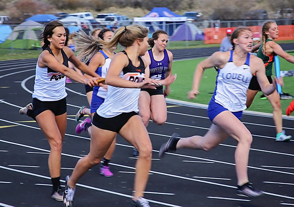 Lady Panther Jaz Haney transfers the baton to Caitlyn Miner while running the 4x100 relay at the Class 3A West Regional Track & Field Meet in Pinedale over the weekend.