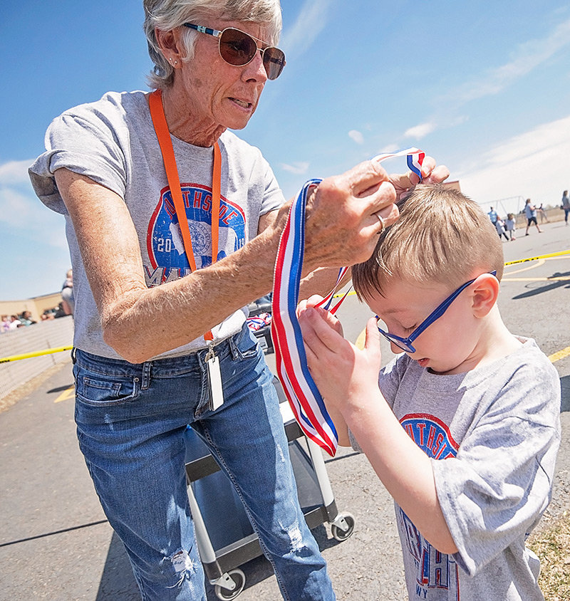Carol Johnston places a medal on marathon finisher Bryson Broadway last month.