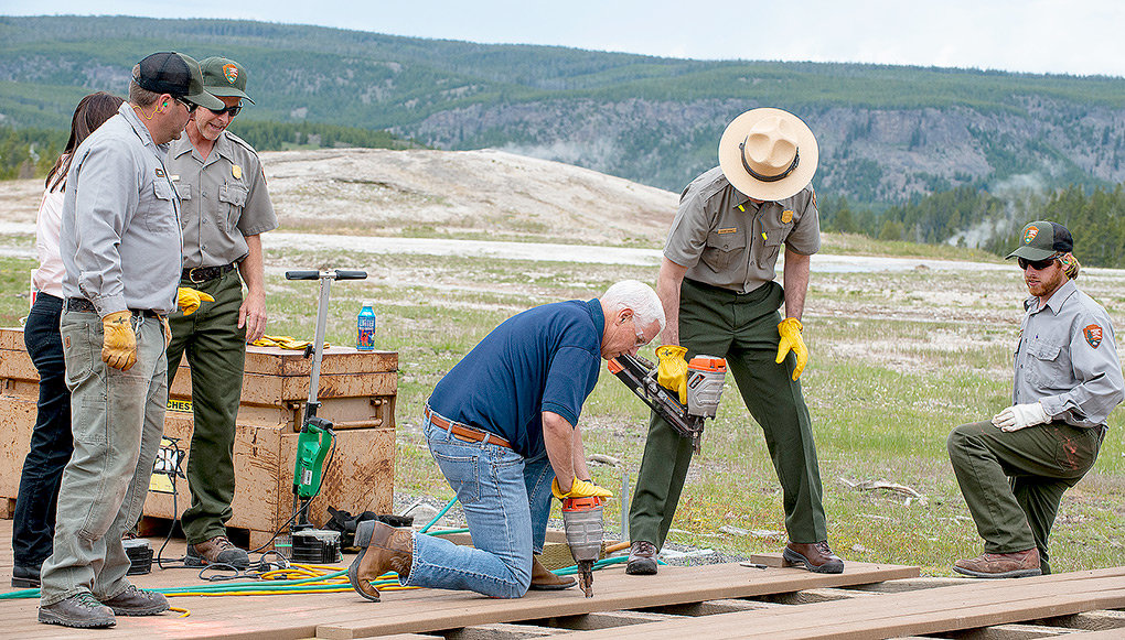Vice President Mike Pence learns to use a nail gun while working on a boardwalk in the public area at Old Faithful Thursday. The work was shortlived, securing a couple boards, and done mostly as a photo opportunity for the media in attendance.