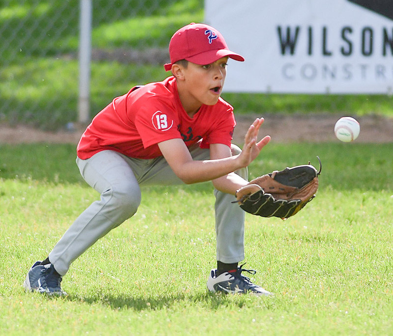 Red Sox outfielder Kaiden Jones fields a hit during the NBHLL championship game against the Lovell Braves.
