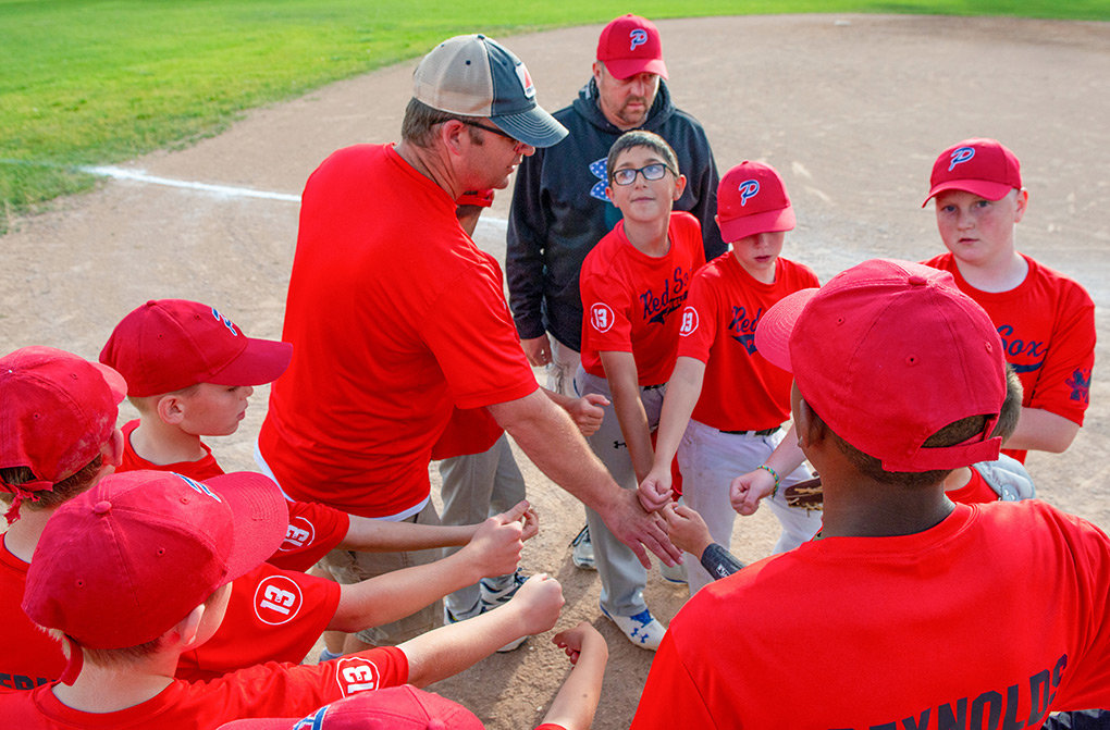 Powell Red Sox head coach Cale Ostermiller (left) and coach Randy Sears gather the players for a pep talk during the Powell Little League championship game against the Powell Rockies on June 26.