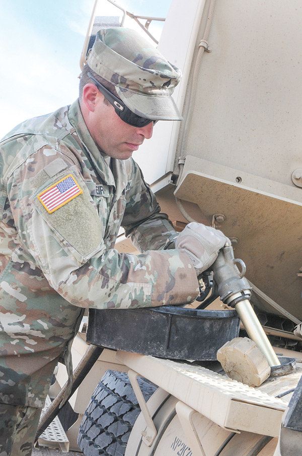 Sgt. Alaor Viera of the Powell-based 960th Brigade Support Battalion, Wyoming Army National Guard, fuels a truck for the 1742nd Transportation Company, South Dakota Army National Guard. The 960th set up a fueling line for the South Dakota unit during a training exercise in June.