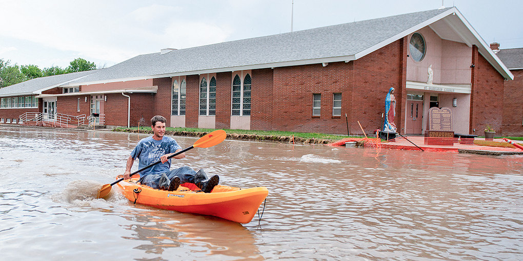 Powell resident Daniel Stanley kayaks south on Absaroka Street near St. Barbara's Catholic Church on Sunday afternoon. Floodwaters filled the construction area with more than a foot of water for several blocks, with the street temporarily resembling a river.
