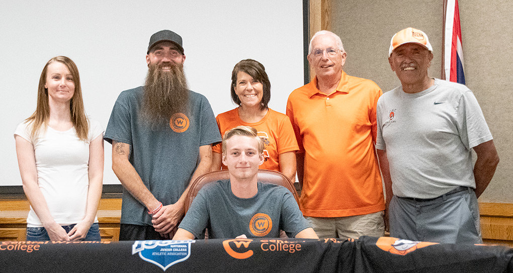 Former PHS cross country and track athlete Jayden Yates (sitting) signs his letter of intent Friday to run for Central Wyoming College next season. Yates is joined by his mother Amanda, father Ty, PHS cross country coaches Ashley Hildebrand and Cliff Boos and CWC cross country coach Al Lara.