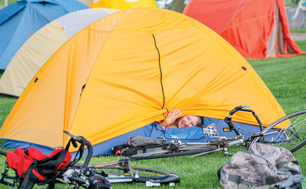 National long distance bicycle record holder Patricia Jones peaks out of her tent while camping at the Powell High School football field Wednesday as part of the Tour de Wyoming.