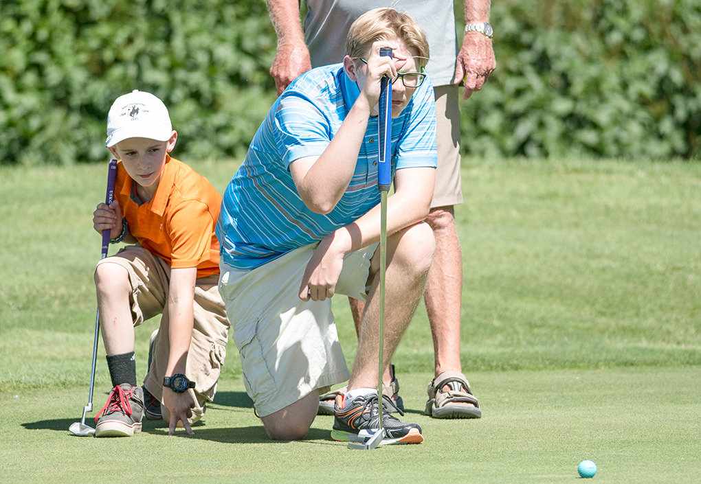 Kirk Thomas, right, lines up a putt as Jacob Thomas looks on during the Members-Juniors Golf Scramble last summer at the Powell Golf Club. Kirk Thomas finished first in the boys' 14-17 division at the Big Horn Basin Junior Tournament earlier this month, while Jacob was seventh in the boys' 11-13 division.