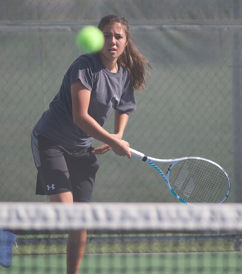 Powell High School tennis player Kaili Wisniewski serves to a teammate Tuesday during a morning practice at the PHS courts. Head coach Joe Asay expects Wisniewski to compete for a varsity spot this season.