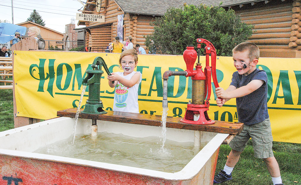 Kit Tidemann (left) and Angus Stukey play with old-fashioned water pumps at last year's Homesteader Days. The festival returns Saturday for its ninth year and will feature a variety of activities for the whole family.
