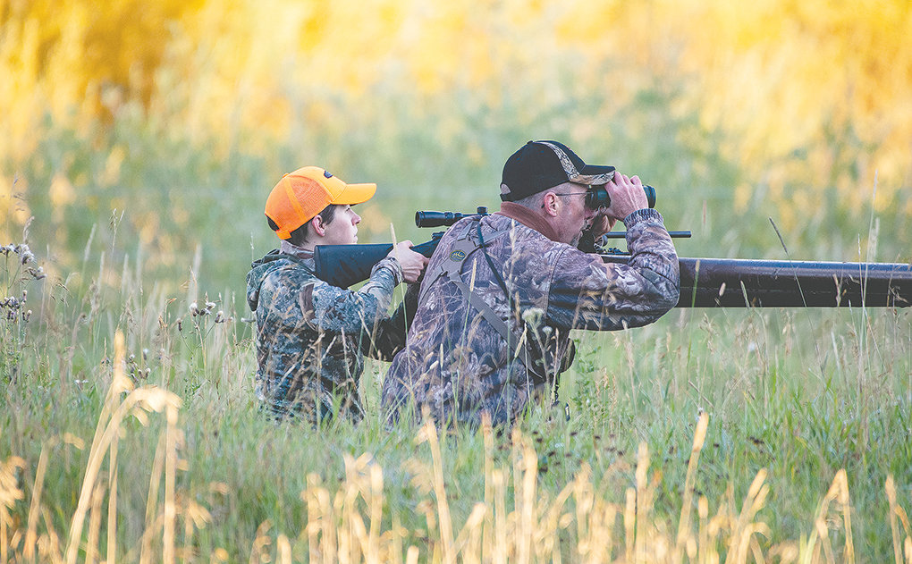Sarah Hamlin watches her target while Fred Williams, hunting mentor and state director for the First Hunt Foundation, looks for an opening while hunting for a doe on Saturday on the Antler Ranch near Meeteetse.