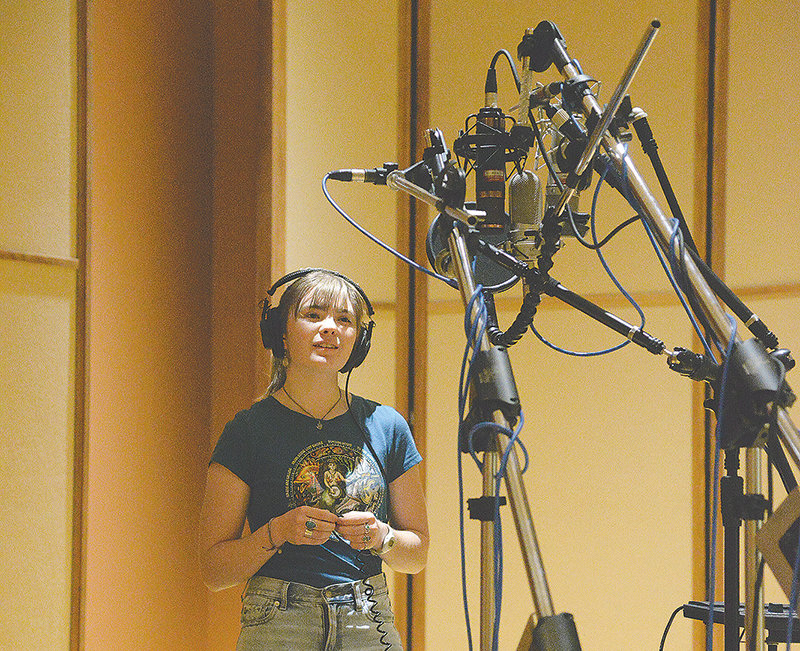 The music technology program collaborates with students from other departments. During a demonstration on microphone properties, Ayla McNeilley sung from different angles and positions in the school's audio recording lab.