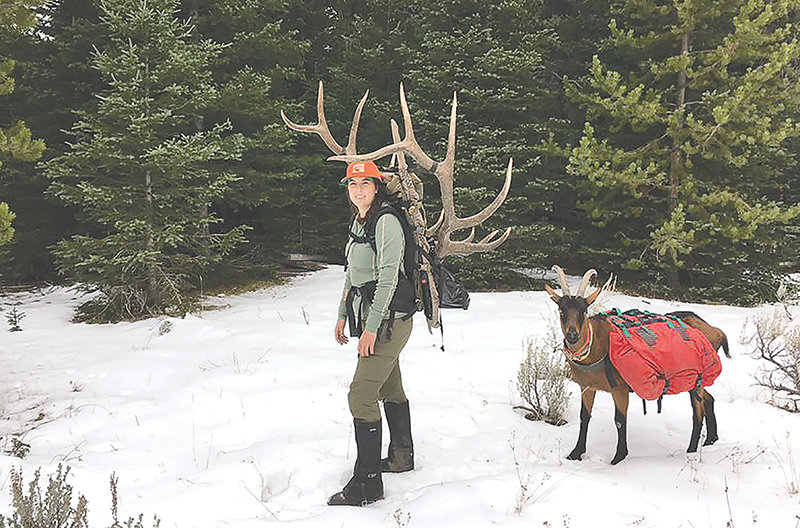 Desarae Starck poses with the head and antlers of her six-point trophy elk Tuesday morning alongside one of her family's goats. Starck is the treasurer for the North American Packgoat Association. She and her husband, Justin, have been training their goats for three years.