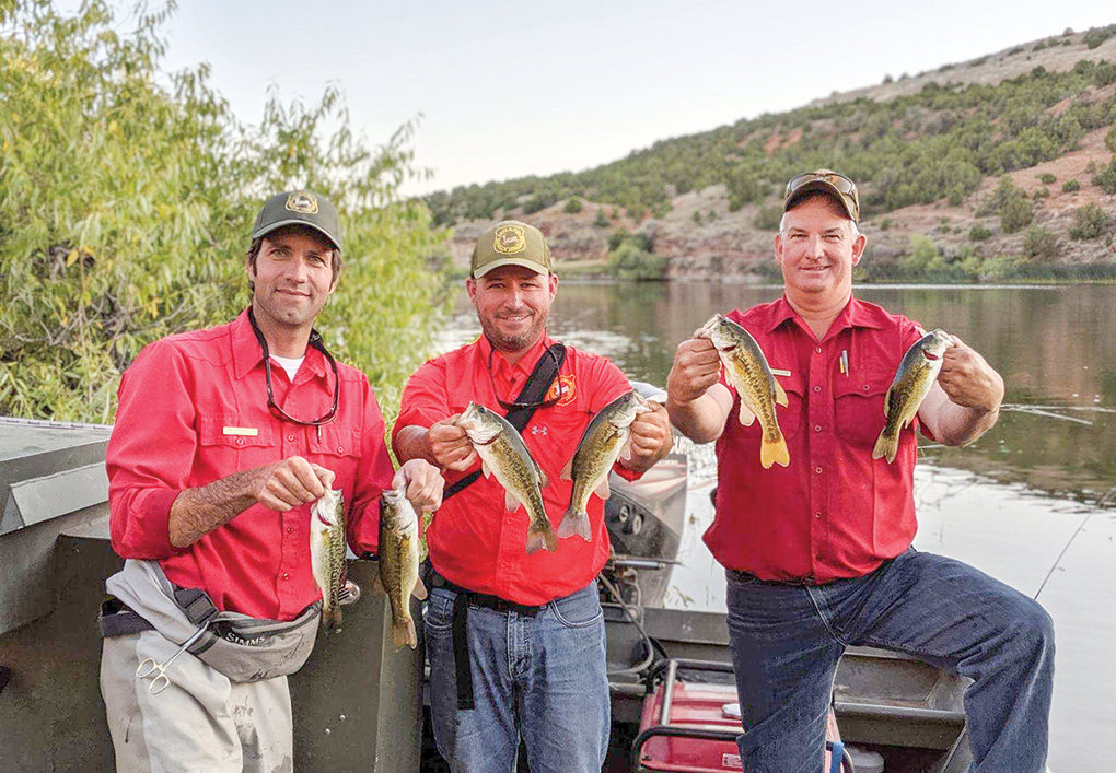 Cody Region Fisheries Supervisor Sam Hochhalter, Assistant Fisheries Management Coordinator Mark Smith and Ten Sleep Fish Hatchery Superintendent Bart Burningham show off some of the largemouth bass recently stocked at Renner Reservoir.