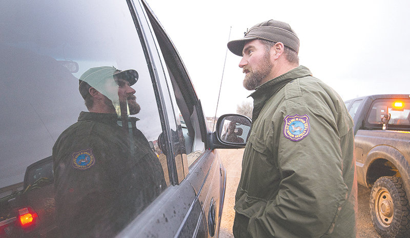 Corey Class, Cody Region wildlife management coordinator for the Wyoming Game and Fish Department, talks with unsuccessful hunters while manning a check station east of Lovell Monday night. The department is asking hunters to submit samples of their deer to be tested for chronic wasting disease.