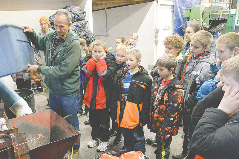 Students in Mark Browning's fourth-grade class at Southside Elementary School are learning about the importance of recycling. They took a field trip this month to the Powell Valley Recycling Center. Here, plant manager Bob Taylor (at left) helps demonstrate how cans are crushed for bailing.