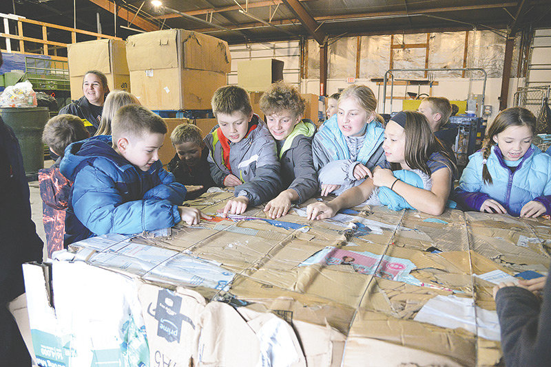 Southside Elementary School students gather around a bundle of cardboard at the Powell Valley Recycling Center during a recent field trip. It was part of a recycling initiative at the school. From left are Jacob Gardner, Jasper Gardner, Renzy Mathews, Breckyn Kobbe, Maddie Croft, Addy Brown and Abigail Visocky.